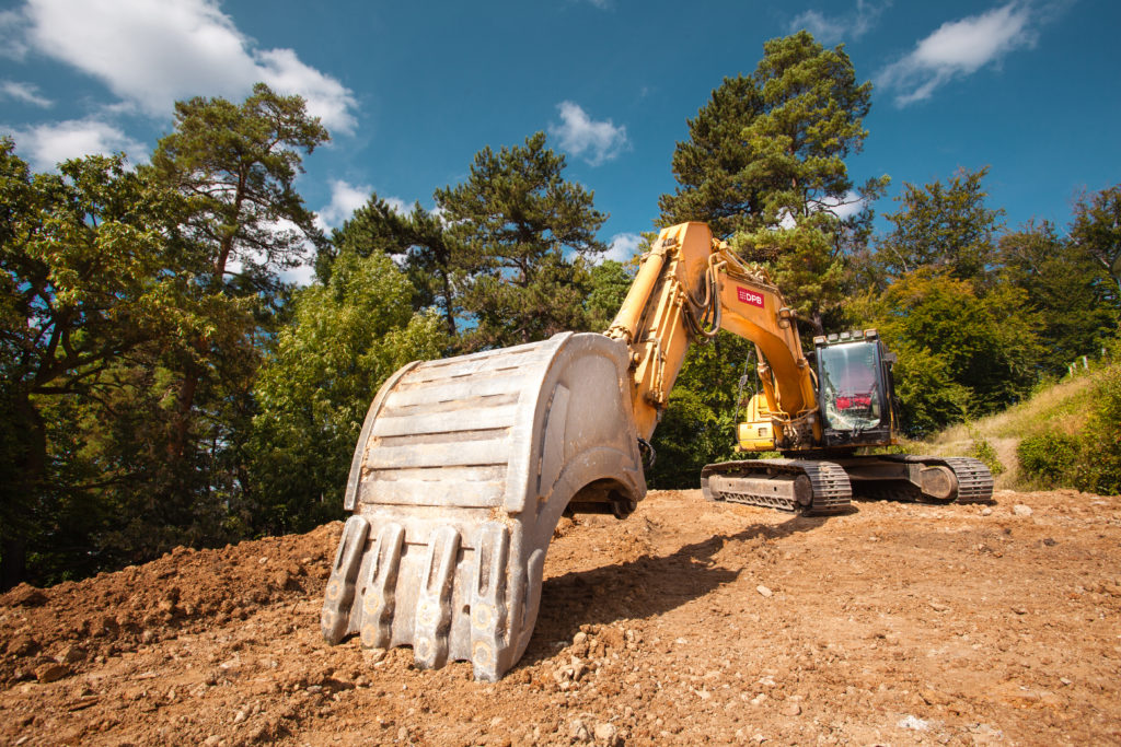 perspective view of excavator on new construction site with trees and blue sky in background